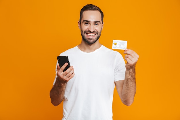 Photo of attractive man 30s in casual wear holding smartphone and credit card, isolated