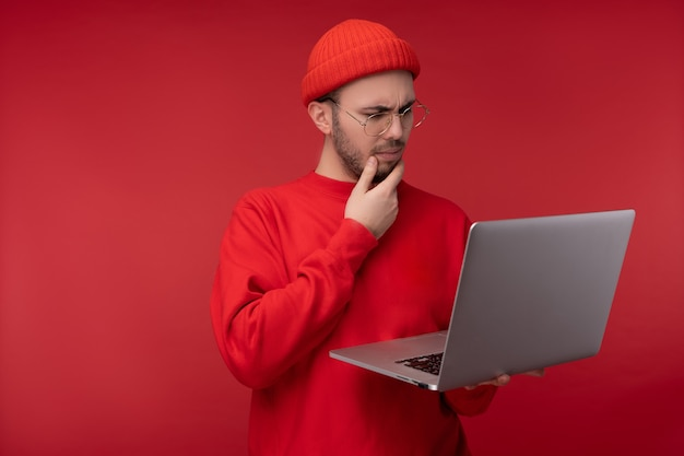 Photo of attractive man with beard in glasses and red clothing. serious man holds laptop and wonders, isolated over red background.