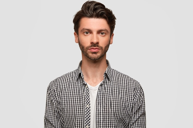 Photo of attractive man with stylish hairdo, has stubble, looks directly seriously, wears checkered shirt, isolated over white wall. confident male manager works, models indoor