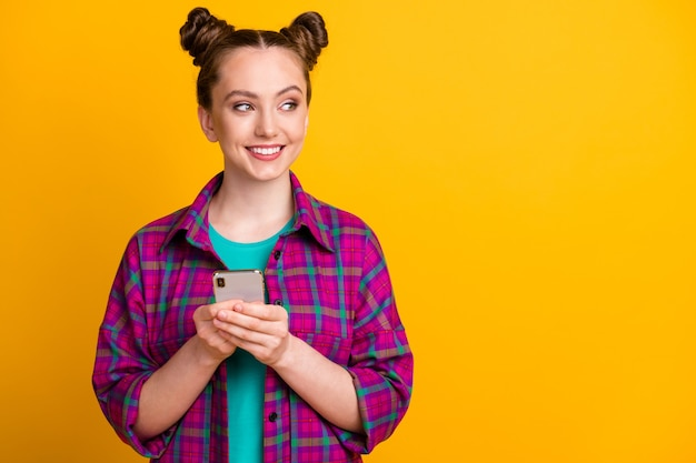 Photo of attractive pretty funny teen lady two buns hold telephone hands good mood blogger look side empty space wear casual plaid magenta shirt isolated yellow bright vivid color background