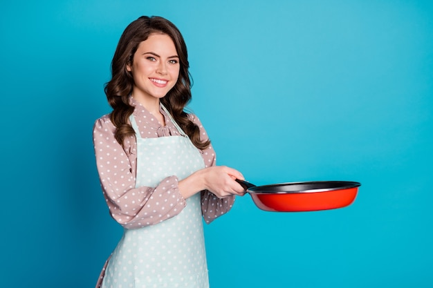 Photo of attractive pretty house wife lady hold hands kitchen frying pan cooking dinner meal is ready show husband his food wear apron dotted dress isolated blue color background