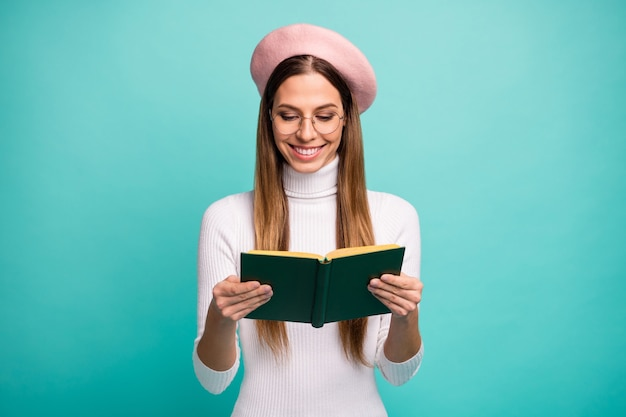 Photo of attractive pretty lady student hold love story book novel interesting plot toothy smiling wear specs modern pink beret white turtleneck isolated bright teal color background