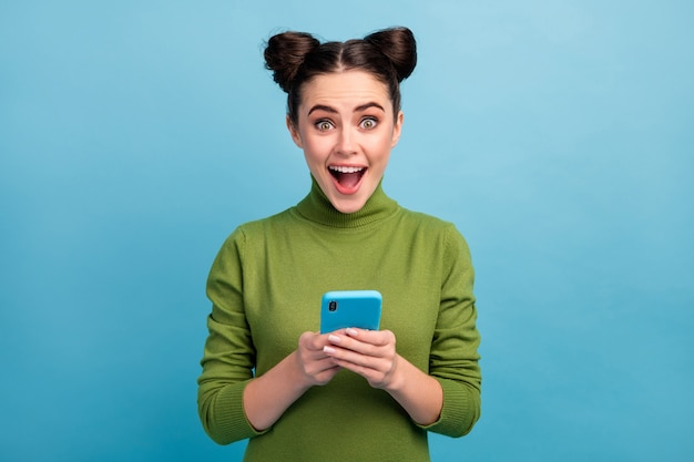 Photo of attractive pretty teen lady open mouth browsing telephone read blog post comments check followers subscribers wear green turtleneck isolated blue color wall