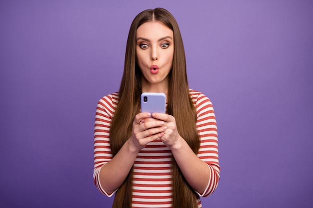Photo of attractive shocked curious lady look open mouth telephone screen read negative comments new blog post wear casual striped shirt isolated pastel purple color wall
