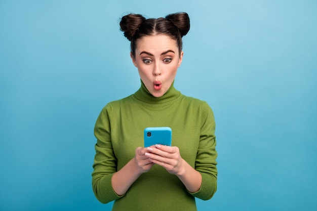 Photo of attractive shocked teen lady open mouth browsing telephone read blog post addicted smart phone user wear green turtleneck isolated blue color wall