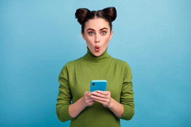 Photo of attractive shocked teen lady open mouth browsing telephone read blog post comments addicted smart phone user wear green turtleneck isolated blue color wall