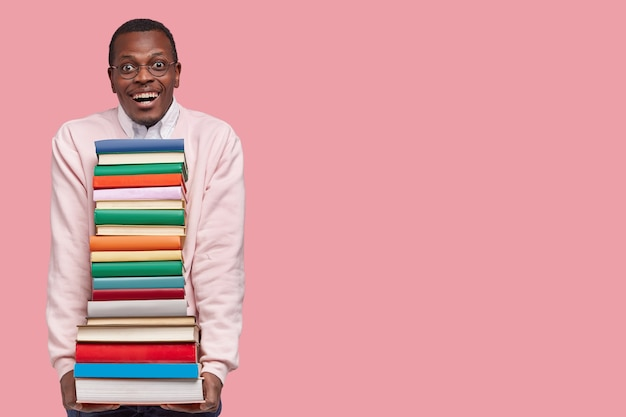Photo of attractive smiling joyful black man in casual jumper holds heap of books borrowed from library