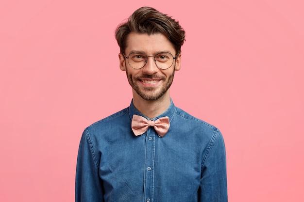 Foto di uomo sorridente attraente con acconciatura alla moda, aspetto positivo, vestito con abiti festivi alla moda, si erge contro il muro rosa