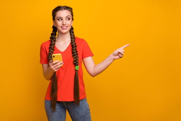 Photo of attractive teen lady hold telephone direct finger side empty space