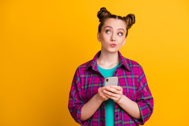 Photo of attractive teen lady two buns hold telephone hands blogger look up dreamy empty space write creative post wear casual plaid magenta shirt isolated yellow bright color background