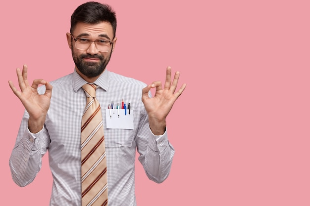 La foto dell'uomo con la barba lunga attraente fa il gesto giusto con entrambe le mani, vestita in abito formale