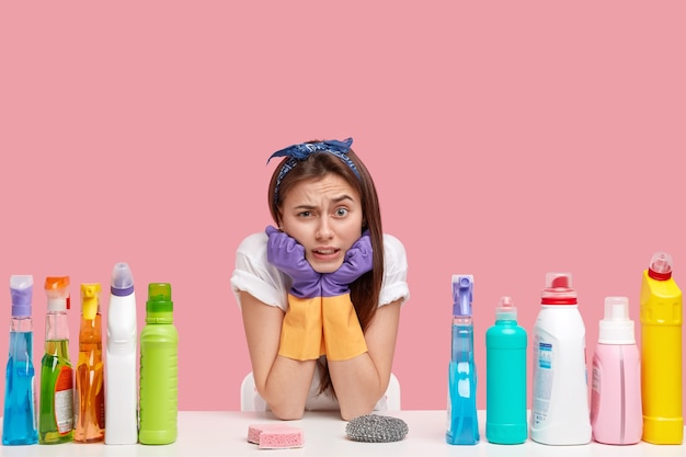 Photo of attractive woman holds chin, frowns face, wears headband, protective rubber gloves, surrounded with cleaning accessories