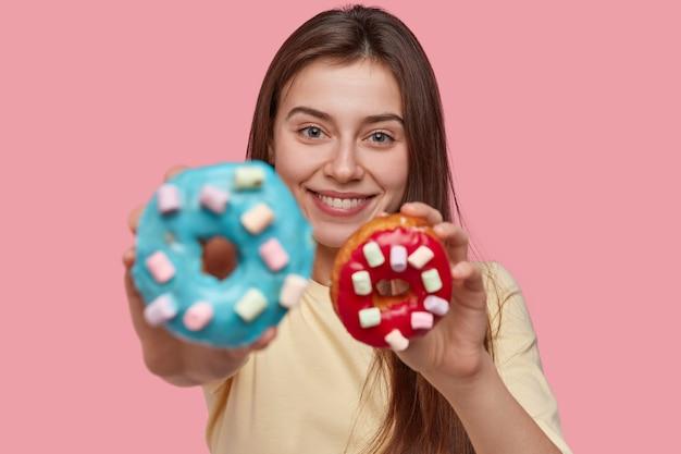 La foto di una donna attraente tiene gustose ciambelle, suggerisce di assaggiare, sorride positivamente, ha un aspetto accattivante