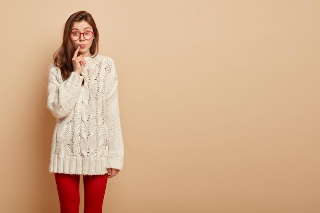 La foto di una donna attraente tiene il dito indice vicino alle labbra piegate, guarda con curiosità, ha un'espressione sorpresa, ascolta informazioni intriganti, indossa un maglione invernale casual, si trova sopra il muro beige