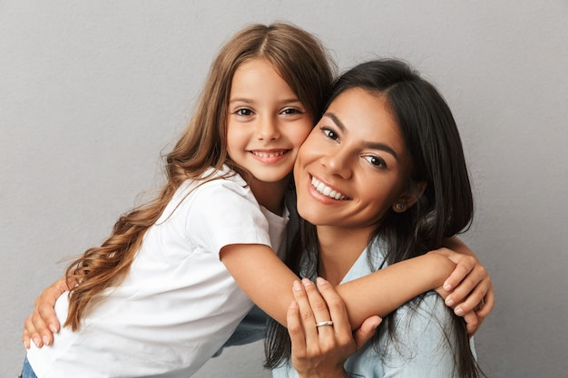 Photo of attractive woman with little daughter smiling and hugging together, isolated over gray