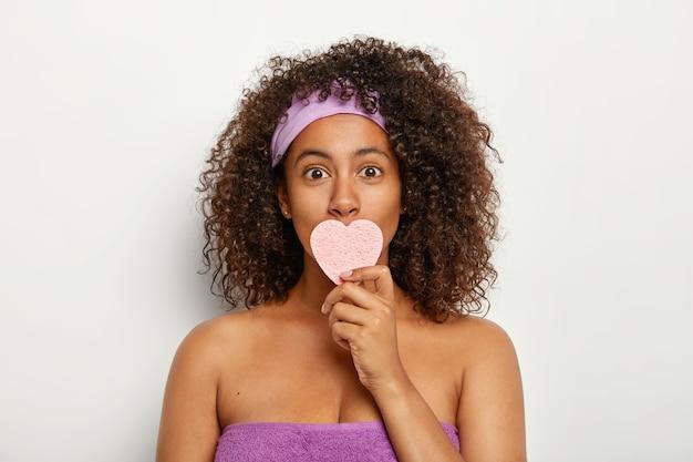 La foto della giovane donna afroamericana attraente indossa la fascia viola e l'asciugamano intorno al corpo, copre la bocca con una spugna cosmetica a forma di cuore, si asciuga il viso