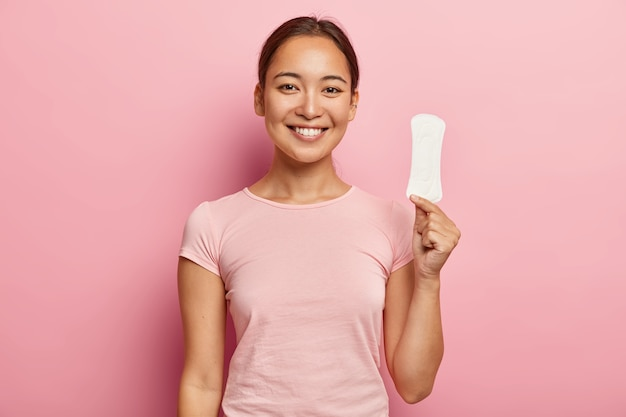 Photo of attractive young lady with asian appearance, holds clean sanitary napkin, satisfied with its quality, uses intimate product during menstruation or periods, isolated on pink wall