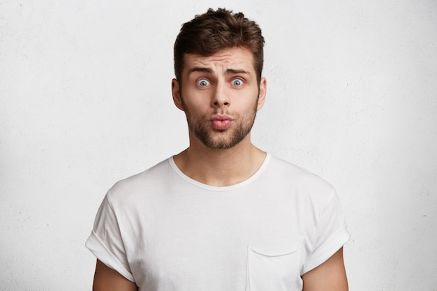 Photo of attractive young unshaven man with innocent expression, looks with blue eyes and rounded lips, begs for forgiveness in girlfriend, feels guilty isolated over white wall