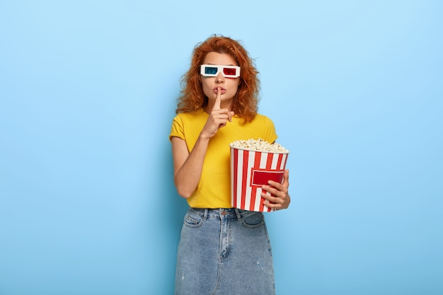Photo of attractive young woman has ginger hair, being in movie theater