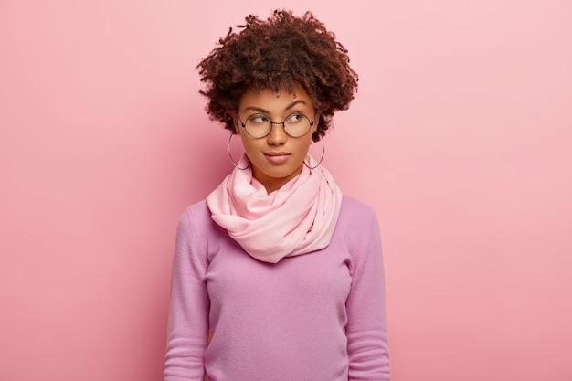 La foto della giovane donna attraente ha un'espressione pensierosa, alza le sopracciglia, guarda da parte, indossa occhiali, maglione viola e sciarpa di seta