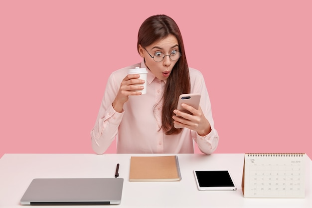 Photo of attractive young woman reads shocking news on mobile phone, watches video in social networks, drinks coffee from disposable cup