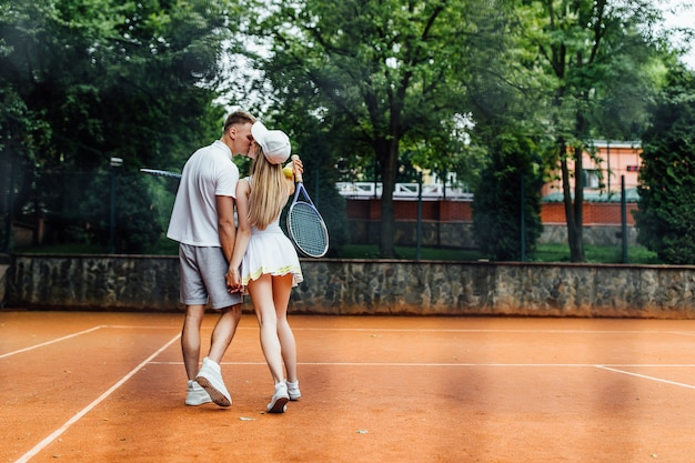 Photo of back. athletic man and slim woman on tennis training, couple after competition..
