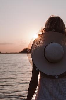На фото сзади блондинка в белом платье молодая красивая счастливая женщина в соломенной шляпе с р ...