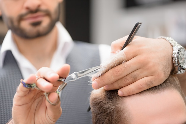 Photo of barber working with client in barbershop.