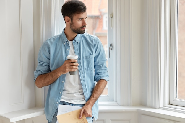 Photo of bearded administrative mamager holds papers, disposable cup of coffee