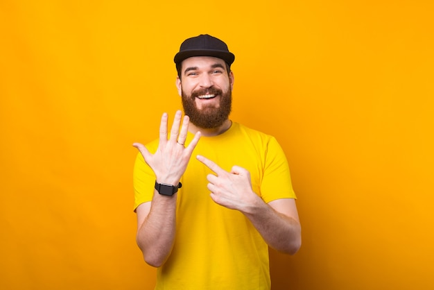 Photo of bearded cheerful man pointing at wedding ring