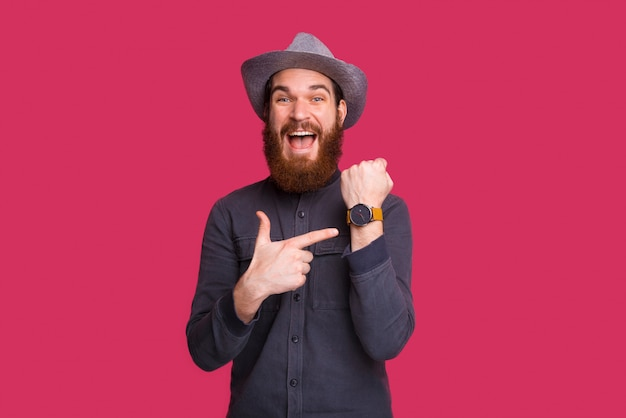 Photo of bearded guy in cowboy hat, excited pointing at watch, standng over isolated space