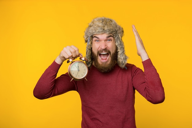 Photo of bearded guy in cozy winter hat, holding a clock, deadline, feeling in hurry and stress, standing over yellow background
