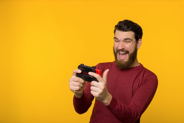 Photo of bearded guy, playing on mobile phone with big pleasure, standing over yellow background