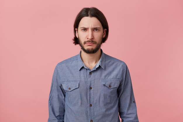 Photo of bearded guy with long dark hair looks sad upset hopeless, ready to cry, pouted his lips, isolated over pink background.