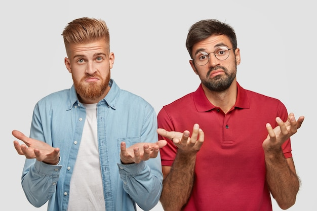 Photo of bearded hesitant men have clueless expression, work together as team, don`t know how to make successful project, wear fashionable clothes and round spectacles, being clever and hard working