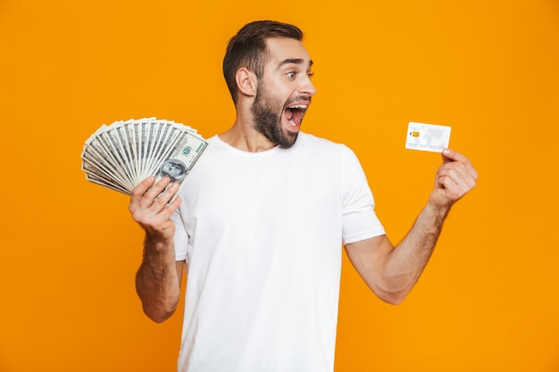 Photo of bearded man 30s in casual wear holding bunch of money and credit card, isolated
