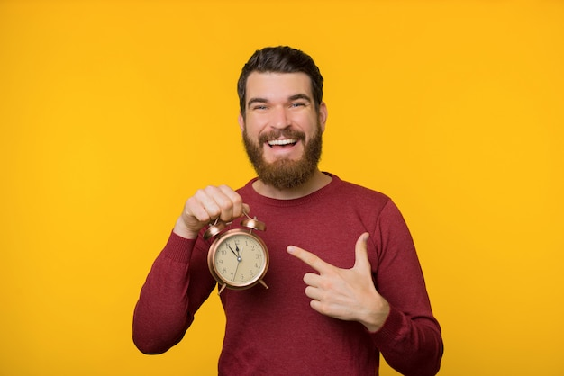 Photo of bearded man, holding and pointing at vintage clock management planning concept