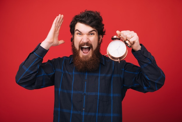 Photo of bearded man, holding a vintage clock, worried about time left. time management and discipline.