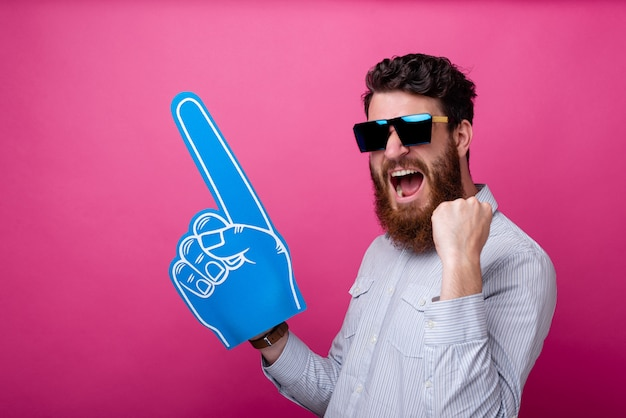 Photo of a bearded man with big blue fan glove pointing away standing over pink background