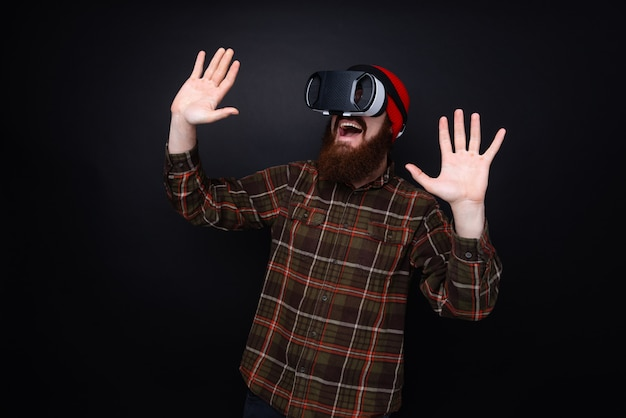 Photo of bearded man with vr glasses,  happy and scared by virtual reality