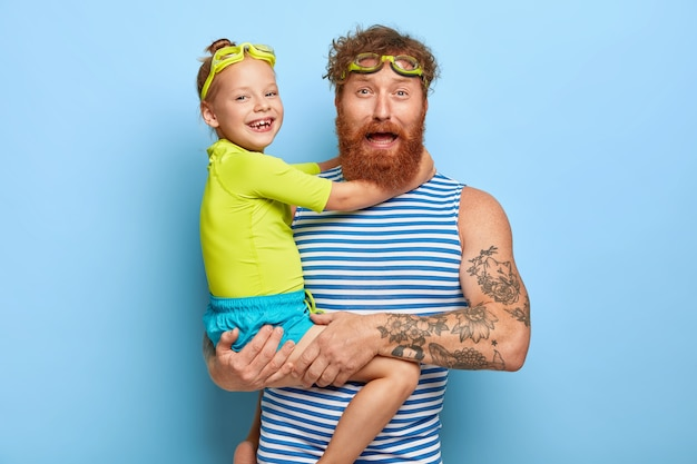 Photo of bearded young father wears goggles and striped vest, carries little daughter, spend summer holidays actively, enjoy swimming, love each other, isolated on blue wall. family concept