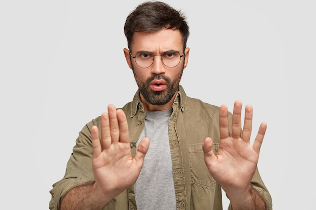 Photo of bearded young male shows stop gesture, has displeased facial expression, denies something, talks about forbidden things, wears fashionable shirt, isolated over white wall