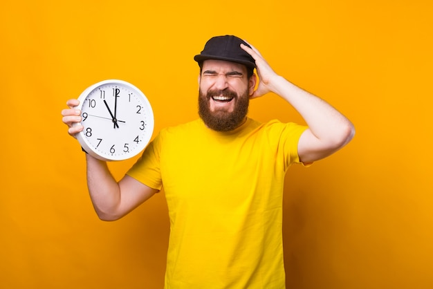 Photo of bearded young man holding wall clock and making frustrating gesture, i am late