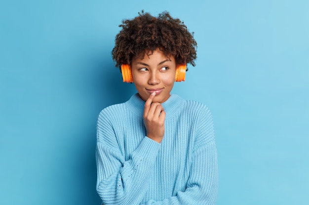 Photo of beautiful african american woman stands thoughtfully indoor listens pleasant song which brings her good memories from past wears casual jumper headphones on ears