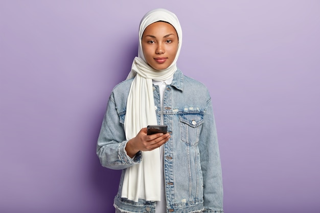 Photo of beautiful arabian woman with dark healthy skin, texts message on modern cell phone, reads comments under post, wears white hijab and denim coat models over purple wall. muslim religion
