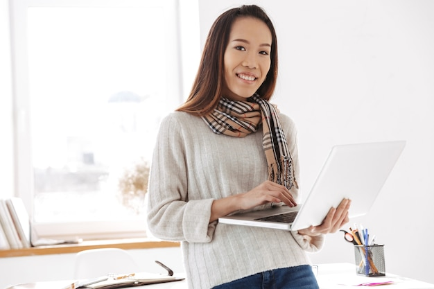 Photo of beautiful asian female worker wearing white sweater holding laptop computer and smiling at camera while sitting on table in office