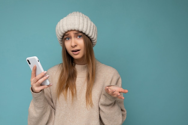 Photo of beautiful asking upset young blonde woman wearing stylish beige warm sweater and knitted