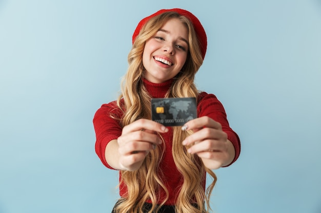 Photo of beautiful blond woman 20s wearing red beret holding credit card isolated