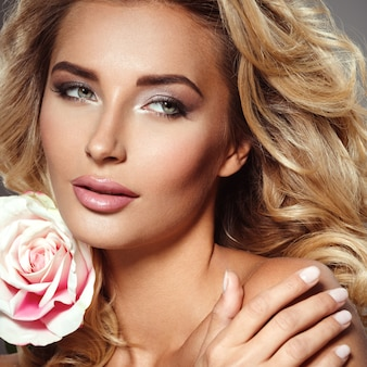 Photo of a beautiful  blond woman with flower. closeup attractive sensual face of white woman with curly hair. smokey eye makeup.