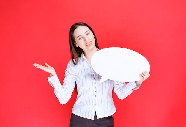 Photo of a beautiful business woman holding an empty speech bubble.